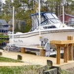 Large white Northern boat is stored on an IMM Quality boat lift rated for 10,000 pounds