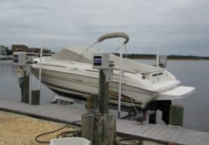 White boat is lowered into the water using a Platinum series beamless boat lift by IMM Quality