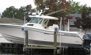 IMM Quality beamless boat lift raises this white boat from the water