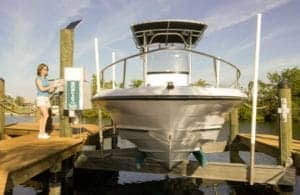 Boat owner uses IMM Quality beamless boat lift and control panel to lower their white boat into the water