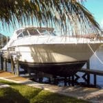 Large white and black boat sits on IMM Quality Boat Lift shaded by palm trees