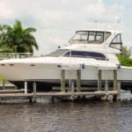 Large white and blue yacht rests securely above brackish water on an IMM Quality Boat lift