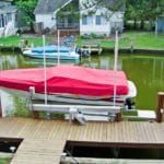 white low profile boat with red cover sits on IMM Quality boat lift along a canal