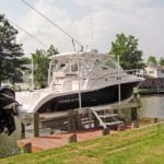 white and black vessel sits on IMM Quality Boat Lift along a canal