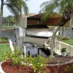 Front view of white boat with canopy sitting on IMM Quality Boat Lift surrounded by palm trees