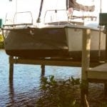 Front view of white catamaran securely stored by IMM Quality Boat Lifts