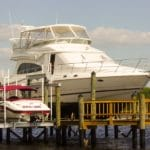Large white yacht and a small white seadoo are both stored on IMM Quality Boat Lifts