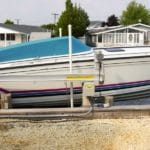 White and blue boat sits on IMM Quality boat lift in front of homes