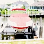 Bright photo of red and white boat sitting on an IMM Quality Alumavator boat lift along a residential canal