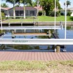 Empty Alumahoist boat lift with dock installation along residential canal