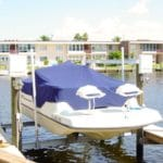 White boat with navy boat cover sits on IMM Quality Boat Lift along residential canal