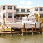Large white yacht is securely stored by an IMM Quality custom boat lift in front of white mansion