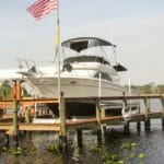 Large white and black boat sits on IMM Quality Boat Lift attached to residential dock