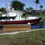 White and red boat named Captiva 24 sits on IMM Quality boat lift attached to wooden residential dock
