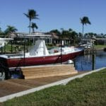 Red boat named Captiva 24 sits on IMM Quality boat lift installed along a residential canal dock