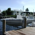 White power boat sits on IMM Quality boat lift on residential dock in Florida