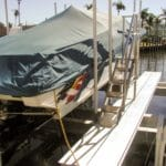 Rear view of covered boat stored securely in marina on an IMM Quality Boat lift