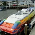 Brightly painted boat with the logo NorTech rests above the water by using IMM Quality Boat Lifts