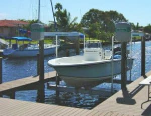 Blue boat rests on Alumavator boat lift with dock installation by IMM Quality Boat Lift