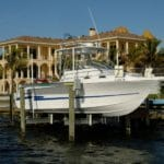 IMM Quality alumahoist boat lift holds a large white yacht in front of large mansion