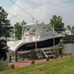 IMM Quality Alumavator boat lift with dock steps holds navy and white fishing boat