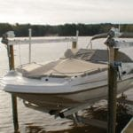 Tan and white boat sits above the water in a canal on an IMM Quality Boat Lift that uses an E drive