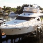 Old IMM Quality Titan yacht lift holds large white yacht securely above canal water