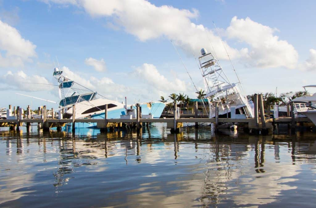 Two leaning boats in marina show the hidden cost of boat ownership after a storm